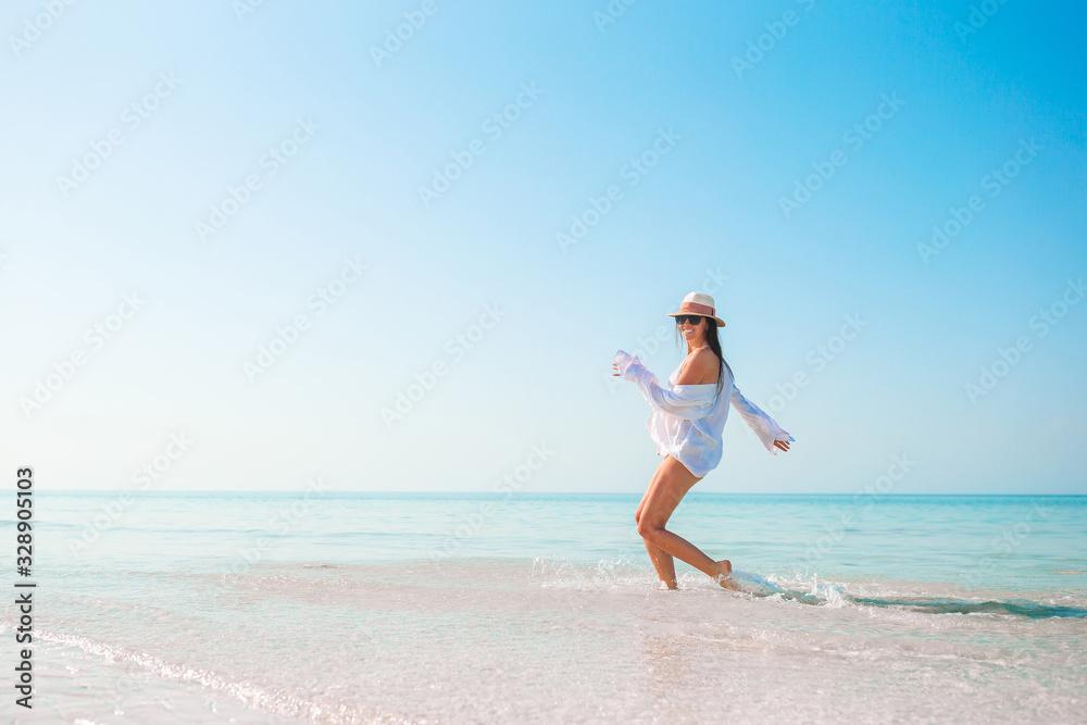 Fototapeta Woman on the beach enjoying summer holidays looking at the sea