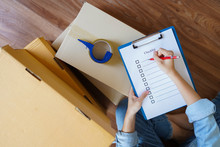 Top View Of Woman Checking Package With Checklist At Home