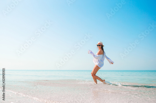 Obraz Woman on the beach enjoying summer holidays looking at the sea - fototapety do salonu