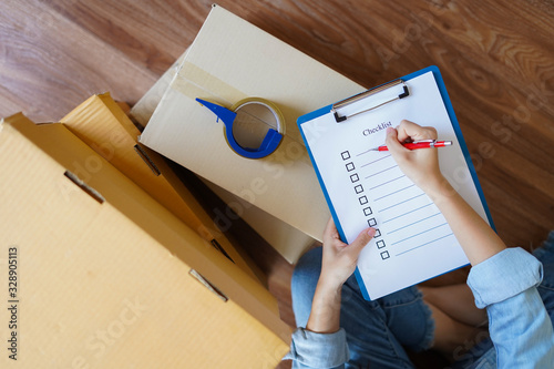 Fototapeta Top view of woman checking package with checklist at home obraz