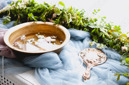 Photo Fancy hand mirror and bowl of water among leaves and flowers prepared for skin c