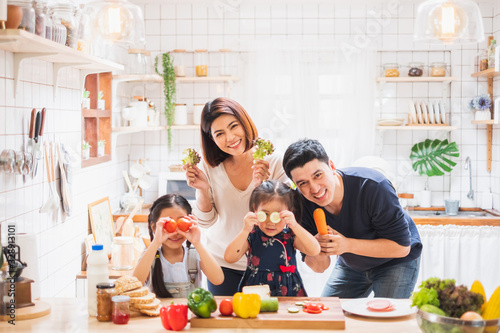 Fototapeta Asian family enjoy playing and cooking food in kitchen at home obraz