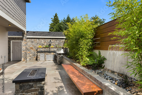 Home exterior backyard hardscape entertainment area with fire pit, bench seating Canvas Print