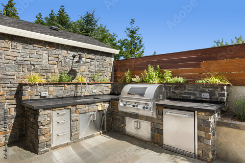 Leinwand Poster Home exterior backyard hardscape outdoor entertainment and cooking area with bar