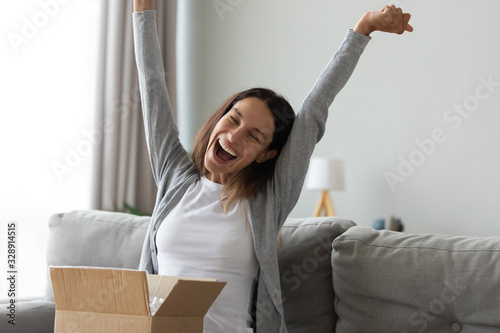 Foto Overjoyed millennial Caucasian girl feel excited unpacking cardboard delivery bo