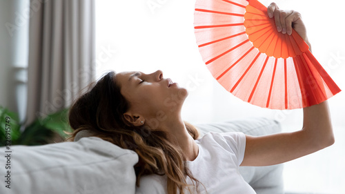 Obraz na płótnie Exhausted young woman sit relax on couch in living room waving with hand fan suf