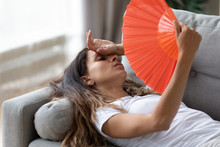 Exhausted Young Woman Lying On Couch In Living Room Using Hand Fan Feeling Sick At Home, Tired Millennial Girl Waving With Hand Waver Suffer From Heatstroke, Lack Of Fresh Air, No Air Conditioner