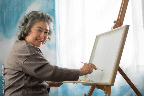 Valokuva Happy smiling Asian Elderly woman oil painting on canvas at house on holidays