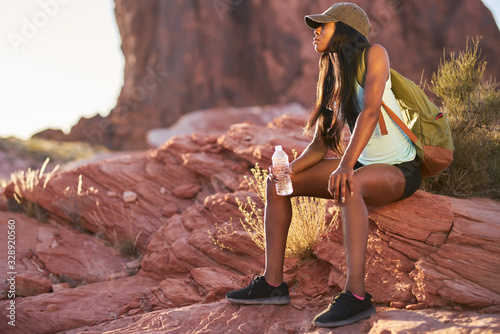 Fototapeta fit african american woman resting with water bottle during hike at valley of fire park obraz