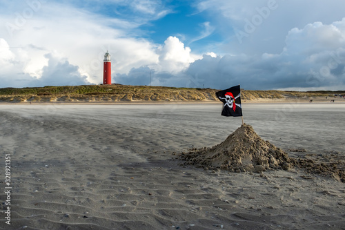 Fotografija Pirate flag and lighthouse on the windswept beaches of Texel