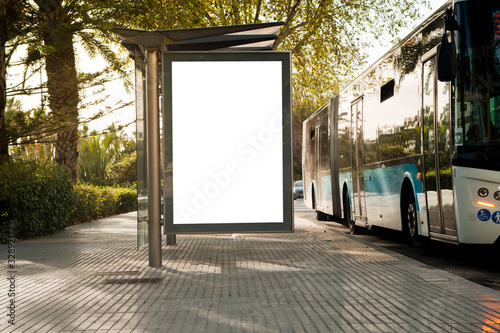 Obraz White blank vertical billboard at the bus stop on the city street. In the background of buses and roads. Sketch. Poster on the street next to the road. - fototapety do salonu