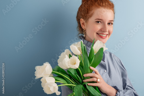 Fotografija Spring beauty, fashion concept: close up studio portrait of young happy smiling natural redhead girl with freckled skin, wearing pearl earrings, ring, holding white tulips