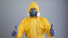 A Man In Yellow Chemical Protection Suit And A Respirator Stands On A Gray Background And Shows A Thumbs Up.