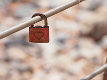 A Red Metal Lock With A Heart Inscription