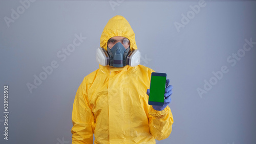 A man in yellow Hazmat suits and a respirator holds a phone with a green screen , gray background Wallpaper Mural
