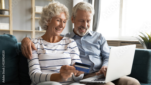 Smiling elderly husband and wife sit on couch make purchases on internet use ban Wallpaper Mural