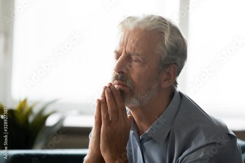Calm hopeful elderly gray-haired man hold hands in prayer ask beg God for better Wallpaper Mural