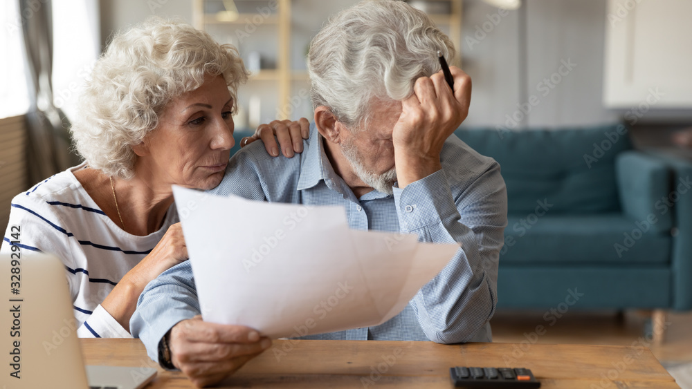 Fototapeta Distressed mature 60s husband and wife sit at table calculate manage household expenses having problems with finances, upset pensioners frustrated troubled with paying bills expenditures