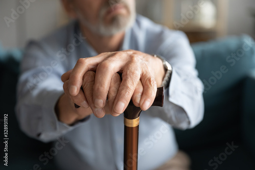 Obraz Close up of old man hands hold wooden cane look in distance thinking pondering, disabled mature 60s male feel lonely abandoned lost in thoughts missing mourning, elderly solitude concept - fototapety do salonu