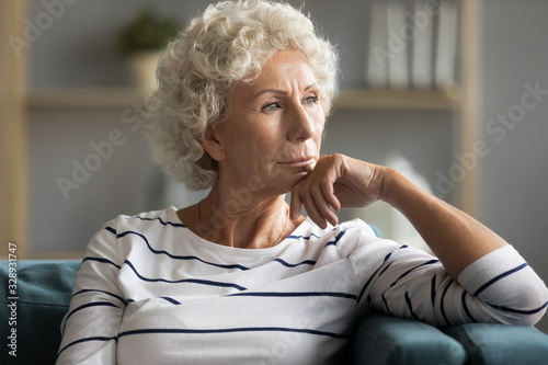 Obraz Pensive middle-aged old lady sit on couch at home look in distance thinking pondering, thoughtful unhappy elderly woman lost in thoughts missing remembering past, feeling lonely, solitude concept - fototapety do salonu