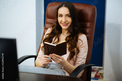 beautiful business woman dark-haired boss with long wavy healthy hair sitting at Fototapet