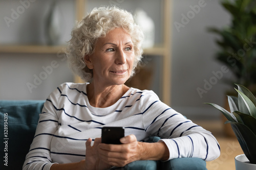 Canvastavla Happy old 50s woman sit on couch at home using modern cellphone gadget look in d