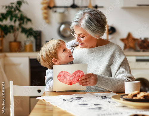 Obraz na plátne happy family grandson child congratulates grandmother on holiday and gives card