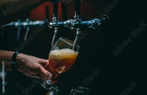 Fotografia bartender hand at beer tap pouring a draught beer in glass serving in a restaura