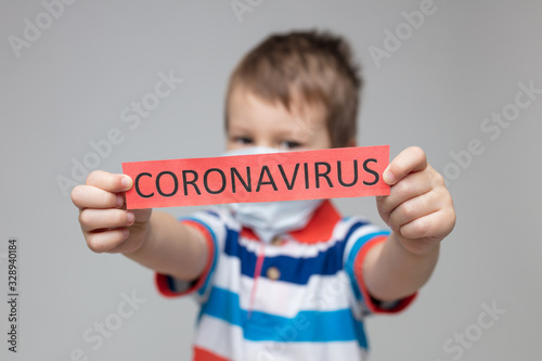 Fotografiet Young child wearing a respiratory mask as a prevention against the Coronavirus C