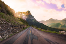 Beautiful Straight Stretch Of Road In Montana With Early Morning Rays Of Sunlight Shining Through The Mountains Onto The Road Ahead