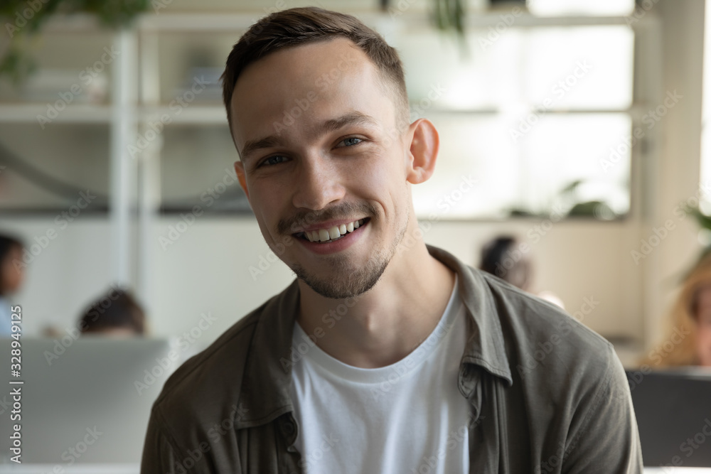 Fototapeta Headshot portrait of smiling millennial male employee talk on video call or web conference in coworking office, profile picture of happy Caucasian young man worker posing in shared workplace
