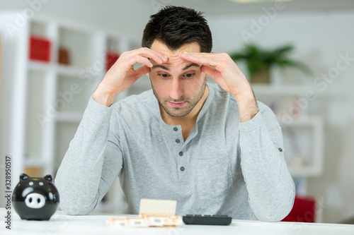 Photo man counting his savings from the piggy bank