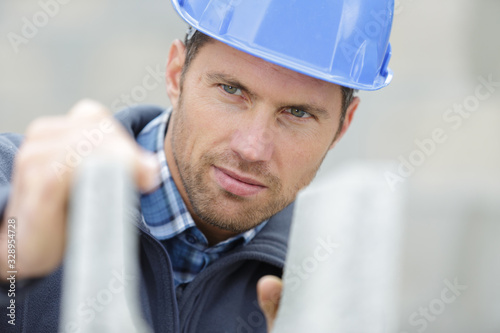 Obraz attractive and confident builder at a constructor site - fototapety do salonu