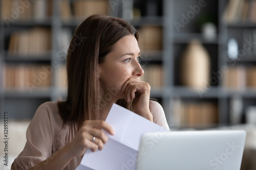Fotografia Head shot stressed young woman holding paper document, bank debt notification, thinking of financial troubles, looking away