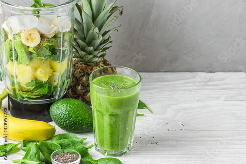 Cuadros en Lienzo Glass of green smoothie detox with fresh juicy ingredients in blender for making
