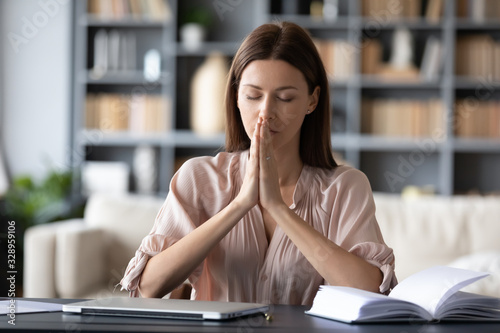 Head shot hopeful employee sitting at table with folded hands, praying before workday start Canvas Print