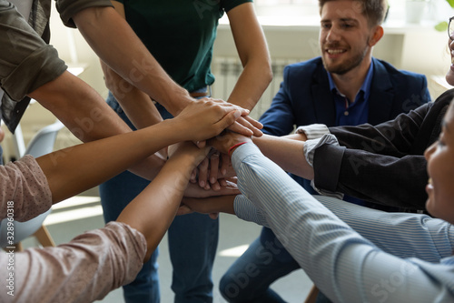 Fototapety, obrazy: Close up of overjoyed diverse businesspeople stack hands engaged in teambuilding activity at briefing, excited multiracial colleagues motivated for shared business success in training at meeting