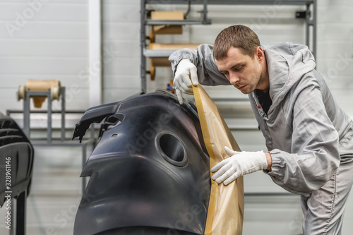 An employee of the paint shop of the automobile plant prepares bumpers for paint Canvas Print