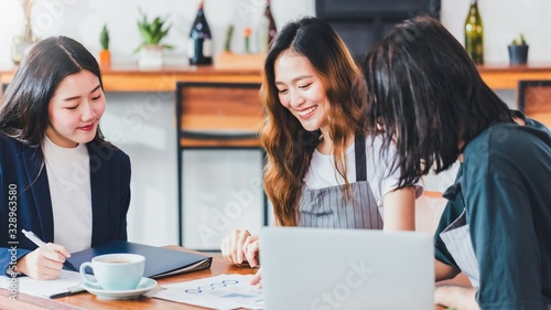 Obraz Asian business women talking about business plan with the coffee shop owner and barista in cafe background.Small business finance concepts For the new generation who wants to startup business. - fototapety do salonu