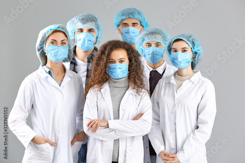 Fotomural Group of doctors with protective masks on grey background