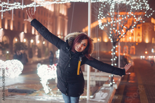 Happy young woman in the city enjoying christmas lights Canvas-taulu