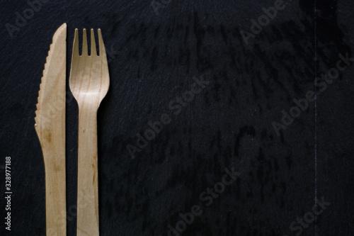 Fotografia, Obraz cuchillo y tenedor de madera en fondo negro, cuchillo y tenedor sustentable