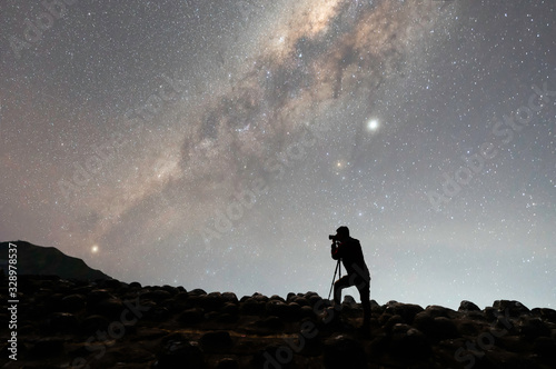 silhouette of photographer with camera next to the Milky Way galaxy on the hill Fototapet