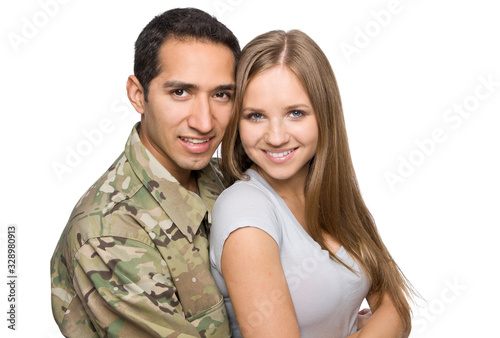 Cute military husband and wife smiling on white background.