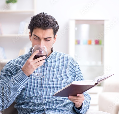 Photo Young man drinking wine at home