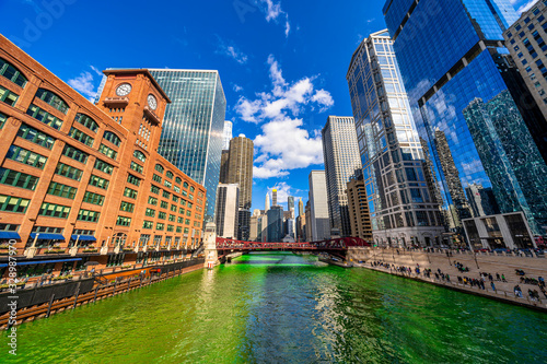 obraz PCV Chicago building and cityscape on Saint Patrick's day around Chicago river walk with green color dyeing river in Chicago Downtown, illinois, USA, crowned irish and american people are celebrating.