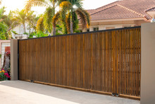 Electric Automatic Wooden Door Or Garage With Modern Home Background. Auto Gate And Remote Control Concept.