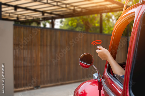 Photo Woman inside red car, hand pressing remote control to open or close the electric sliding auto door