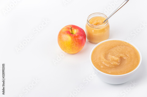 Fresh homemade applesauce in white bowl and jar with fruit puree on white table Wallpaper Mural