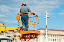 Worker In Cherry Picker Bucket At Height Against Blue Sky. Height Construction Worker Repair Street Light Pole. Electrician Standing In Mobile Crane Bucket While Rises To Repair Wiring.